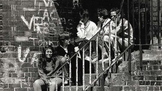 Young people sitting on steps outside a graffitied building in the 1980s